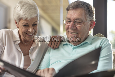 happy senior couple sitting on couch