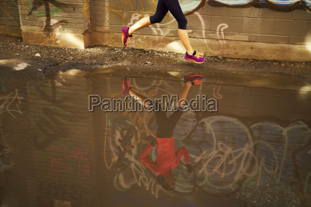 woman running past puddle in graffiti