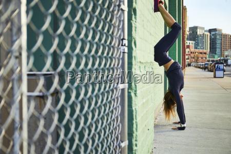 woman doing handstand on sidewalk beside