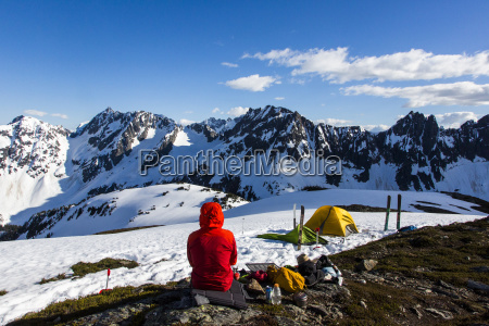 man camping in snowy mountains at
