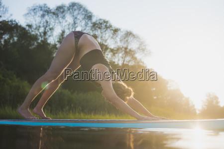 young woman doing sup yoga at