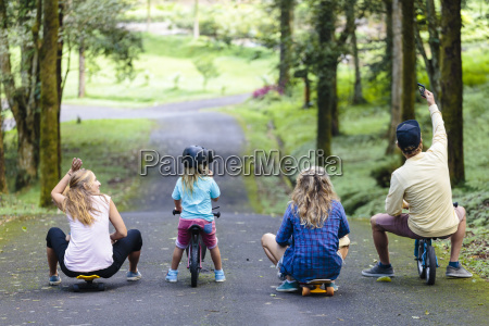 family with skateboards and bicycles taking