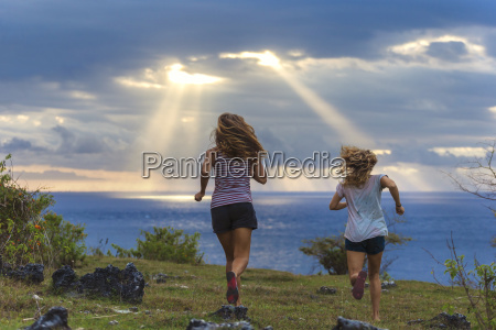 two young women running by sea