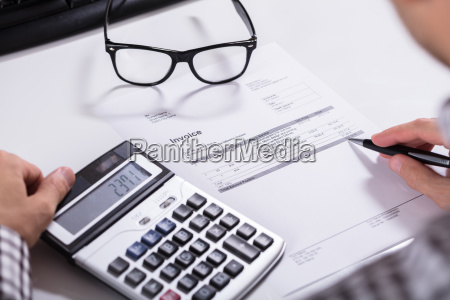 businessmans hands calculating invoice