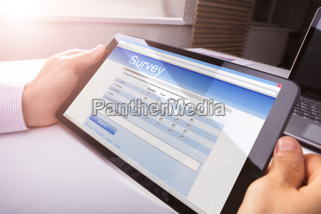 persons hand holding digital tablet showing