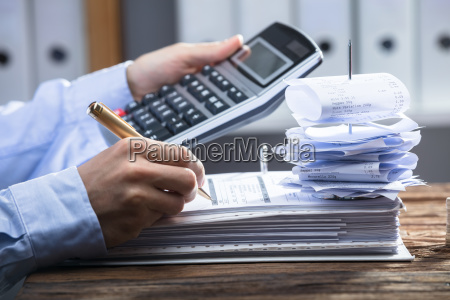 businessperson using calculator for calculating invoice