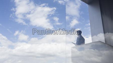 nachdenklicher geschaeftsmann steht auf modernem balkon