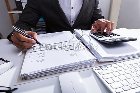nahaufnahme eines wirtschaftlers der rechnung berechnet