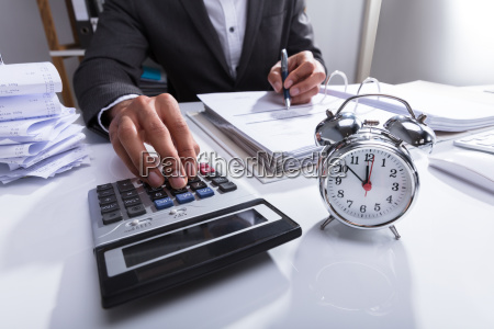 businessperson using calculator for calculating bill