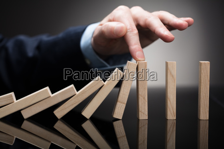 businessperson stopping wooden blocks from falling