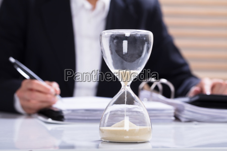 hourglass with businesswoman calculating bill