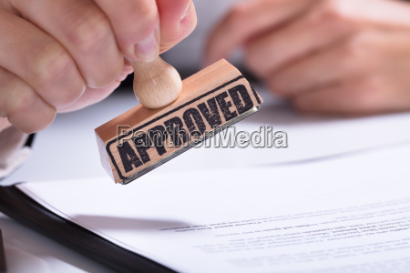 person hands using stamper on document