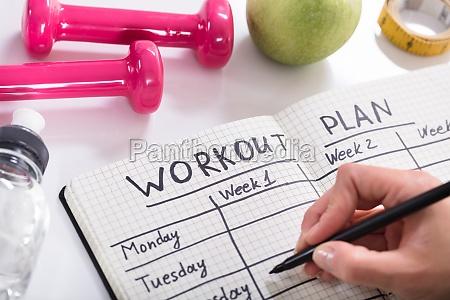 trainingsplan im notizbuch am hoelzernen schreibtisch