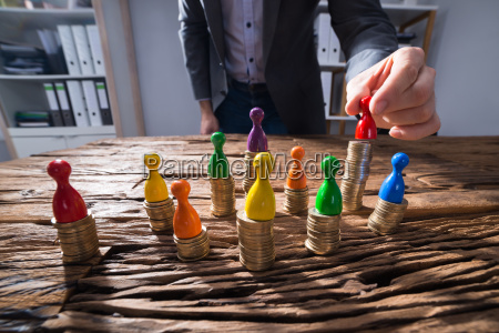 businessperson placing red figurine pawn on