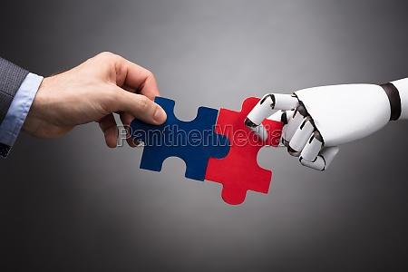 businessperson und robot holding jigsaw puzzle
