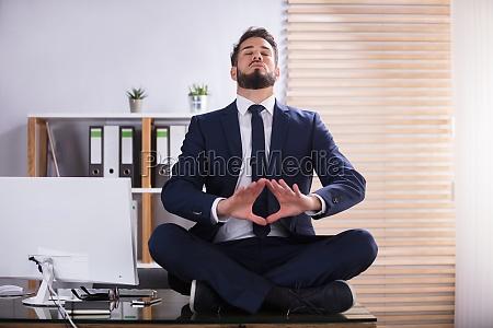 geschaeftsmann machen yoga im buero
