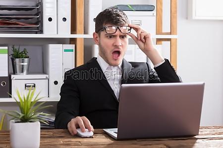 shocked businessman looking at laptop
