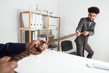 two businessmen playing tug of war