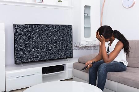 frau die auf sofa nahe fernsehen