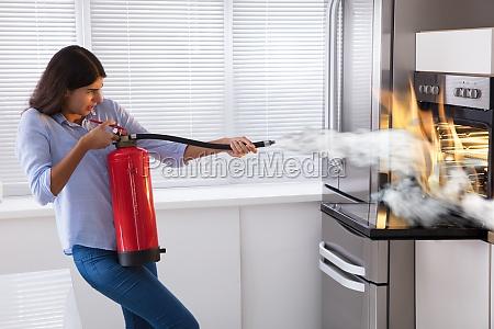 frau die feuerloescher verwendet um feuer