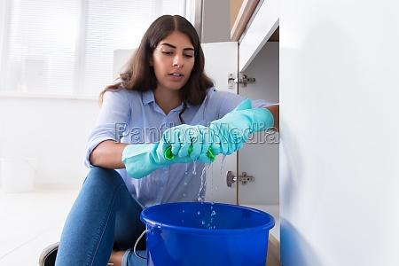 frau die wasser im eimer zusammendrueckt
