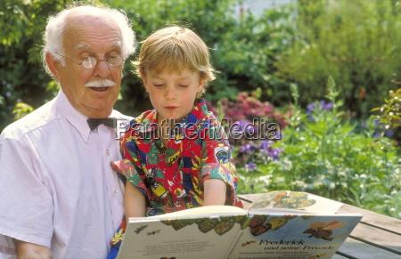 portrait grossvater liest im garten seinem