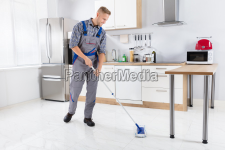 young male worker mopping floor