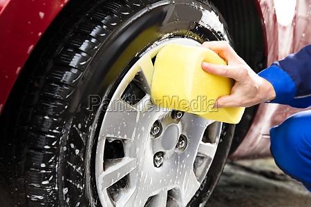 worker hands washing car wheel