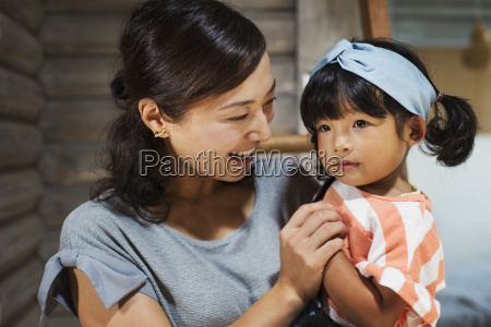 smiling woman holding young girl with