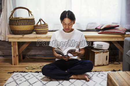 man sitting indoors on a rug