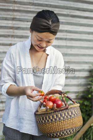 smiling woman standing outdoors holding basket