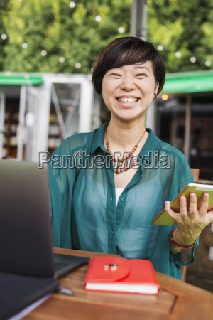 woman with black hair wearing green
