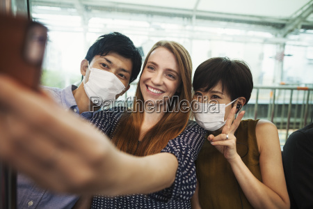 three people two with dust masks