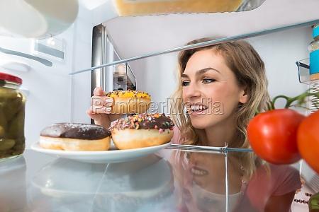 glueckliche frau die donut von der