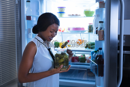 young woman eating pickle