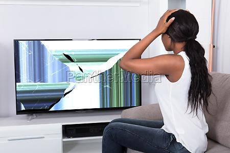 umgekippte frau die gebrochenen fernsehbildschirm betrachtet