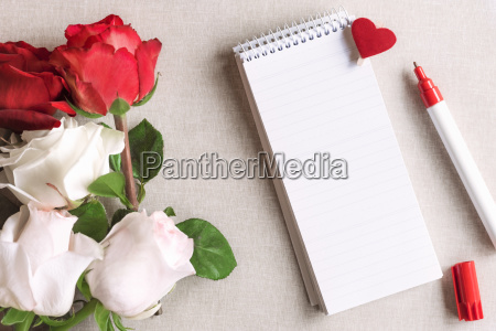 roses and a blank spiral notebook