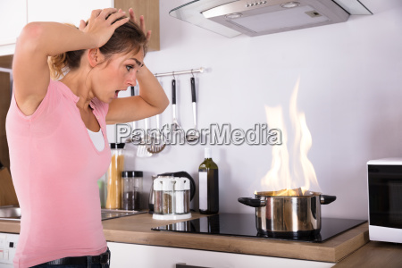 shocked young woman looking at cooking