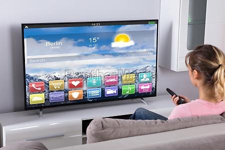 woman sitting on sofa using remote
