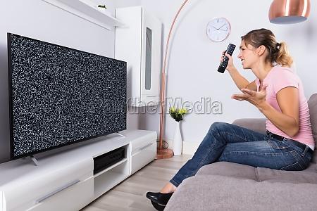 frau frustriert mit einem tv bildschirm