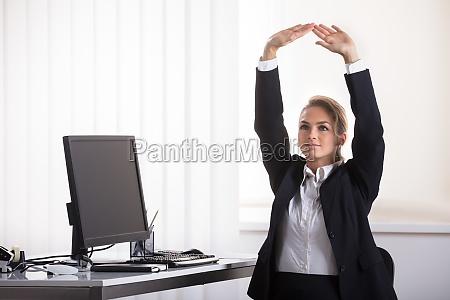 geschaeftsfrau die auf dem stuhl ausdehnt
