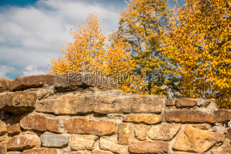 strong stone wall and yellow autumn