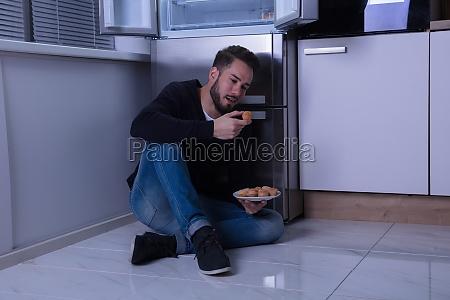 man sitting on floor eating cookie