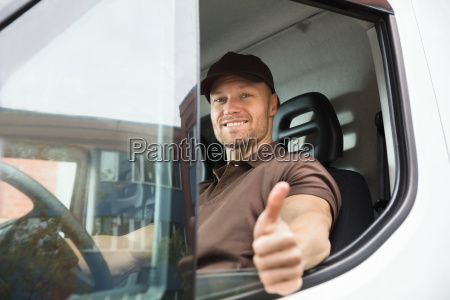 happy delivery man sitting inside van