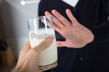 person rejecting glass of milk
