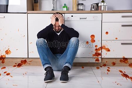 man sitting on kitchen floor with