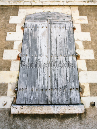windows closed by wooden shutters in
