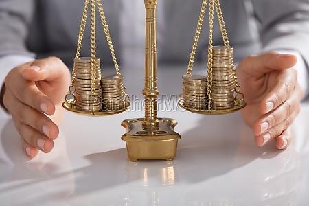 businessperson schuetzt justizskala mit gestapelten muenzausfaellen