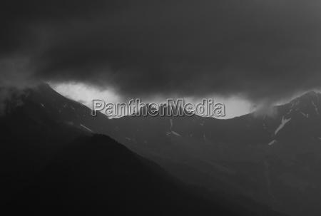 dark storm wolken ueber eine bergkette