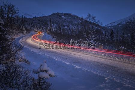 fahrzeugruecklichtspuren auf einer schneebedeckten strasse im